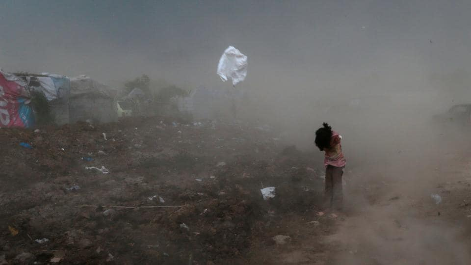 A girl protects herself from garbage and dust, raised by a gust of wind, in a slum in Islamabad, Pakistan. (Caren Firouz  / REUTERS)