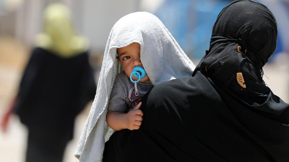 A picture taken on June 5, 2017 shows a displaced Iraqi woman carrying a child at the Al-Khazir camp for internally displaced people, located between Arbil and Mosul. Tired and traumatised, Iraqi mothers who fled Mosul struggle to breastfeed or buy baby formula milk for their babies. / AFP PHOTO / KARIM SAHIB
