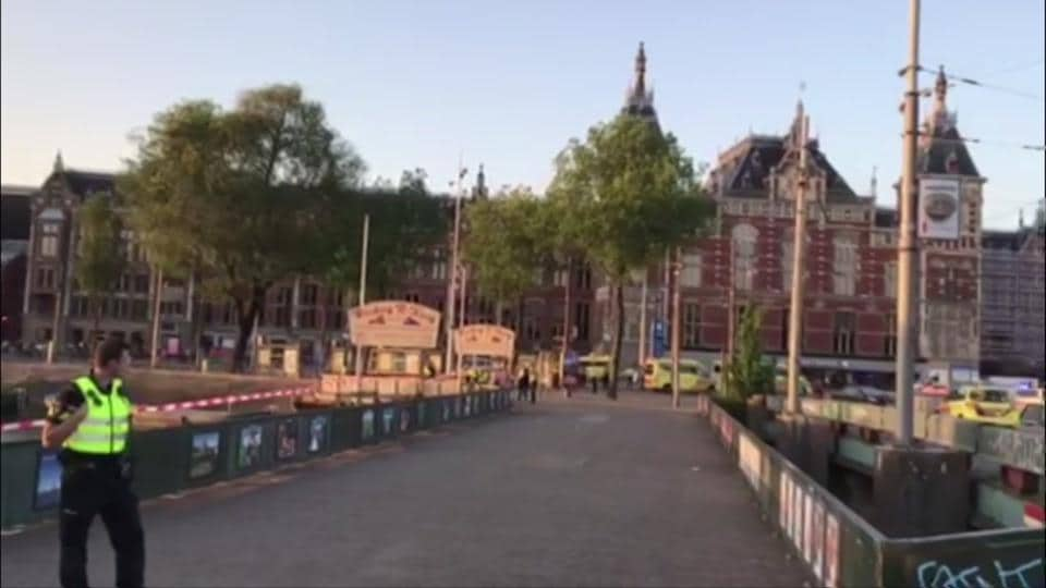 This image taken from video shows a security officer standing outside Amsterdam Centraal Station in Amsterdam, Saturday, June 10, 2017.