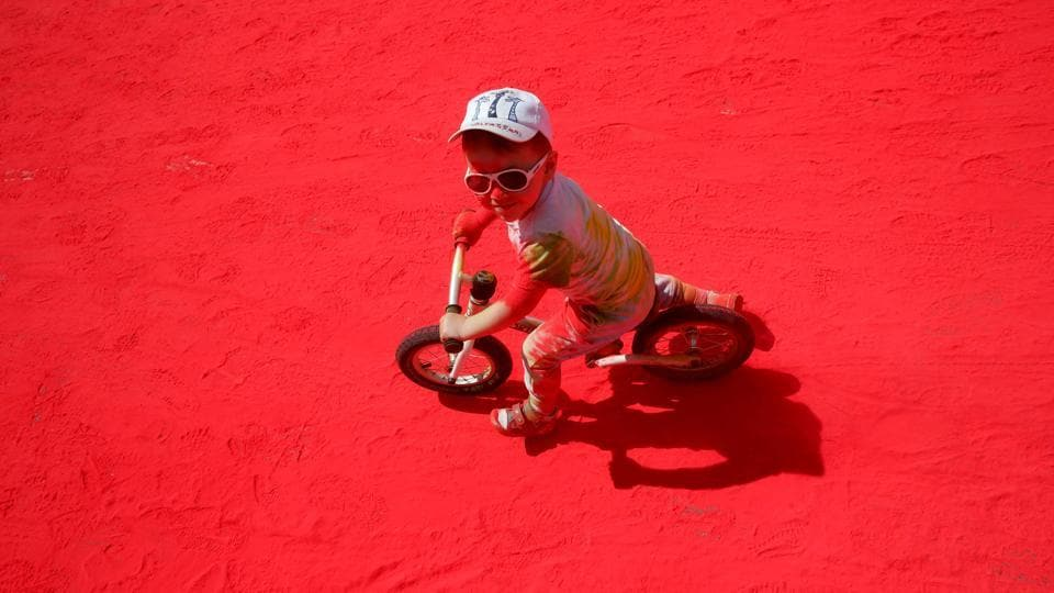 A boy rides his  bicycle over red powder during the  run. (Maxim ZMEYEV / AFP)