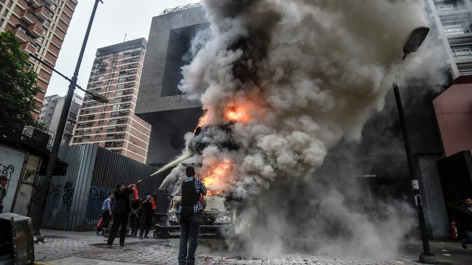 Employees of the administration headquarters of the Supreme Court of Justice try to put out the fire of a burning vehicle during a demo in Caracas. The head of the Venezuelan military, General Vladimir Padrino Lopez, who is also President Nicolas Maduro's defence minister, is warning his troops not to commit