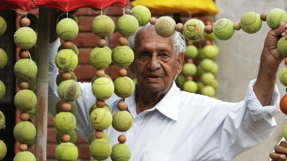 It was in the early 1960s that he began to clear a little forest patch near Sukhna Lake to create a small garden.  Here he seems to be holding up a string of old tennis balls from a creation at Chandigarh lawn tennis association's complex in Sector 10.  (HT File Photo)