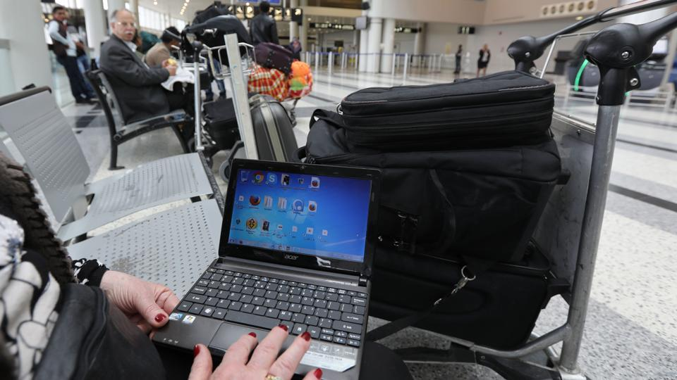 This file photo taken on March 22, 2017 shows a Syrian woman travelling to the United States through Amman opens her laptop before checking in at Beirut international airport.