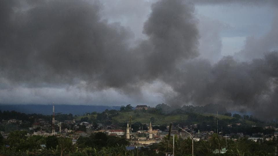 In this June 9 photo, black smoke from continuing military air strikes rises above a mosque in Marawi city, southern Philippines.