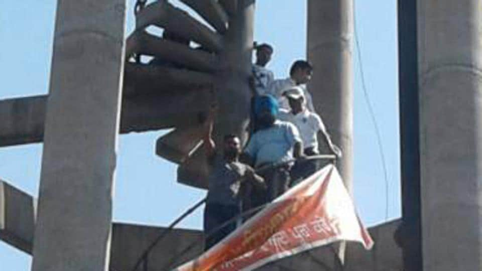 Siksha providers protesting against the non-payment of salaries on a water tank in Dinanagar on Sunday.