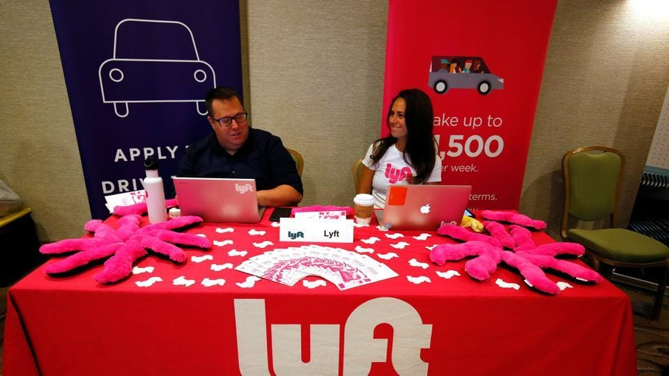 Recruiters for Lyft wait for the opening of a job fair in Golden, Colorado.