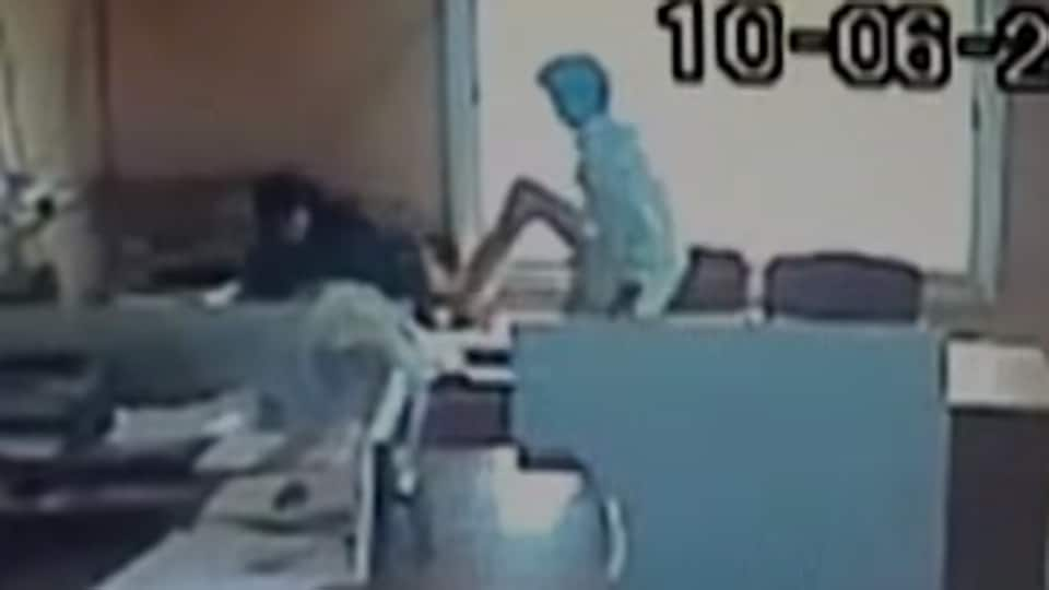 An employee kicks a female colleague at Sindhanur city corporation in Karnataka's Raichur.