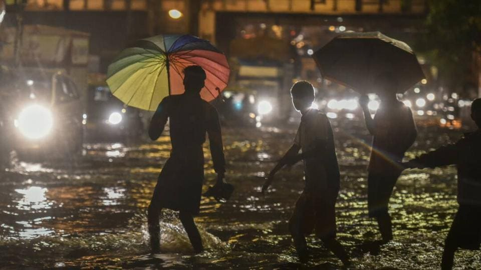 People walk through a water-logged street as it rains at Sion in Mumbai on Monday