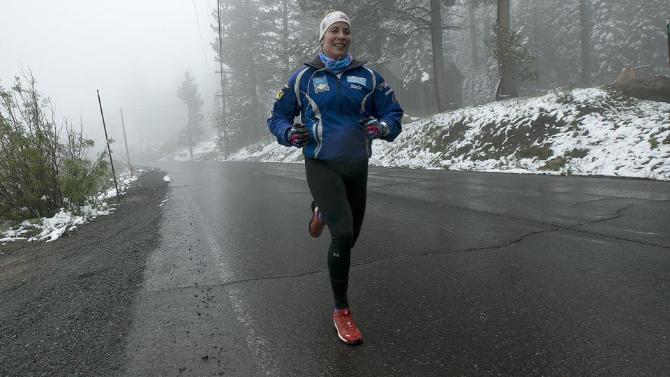 Christina Mishica runs along fog shrouded Highway 40  near Soda Springs, Calif. (Rich Pedroncelli / AP)