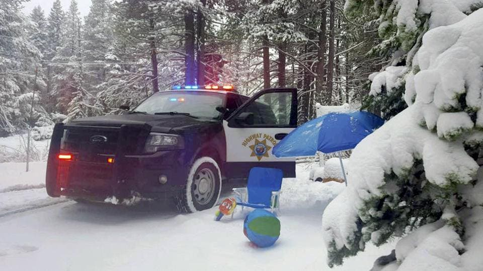 California Highway Patrol Truckee office, a highway patrol vehicle is stopped in the snow next to an umbrella and lawn chair near the Donner Summit rest area . (Randy Fisher / AP)