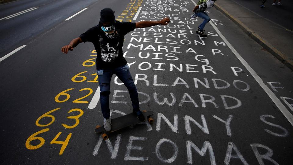 Demonstrators roll on skateboards on a list of the victims.  (REUTERS)