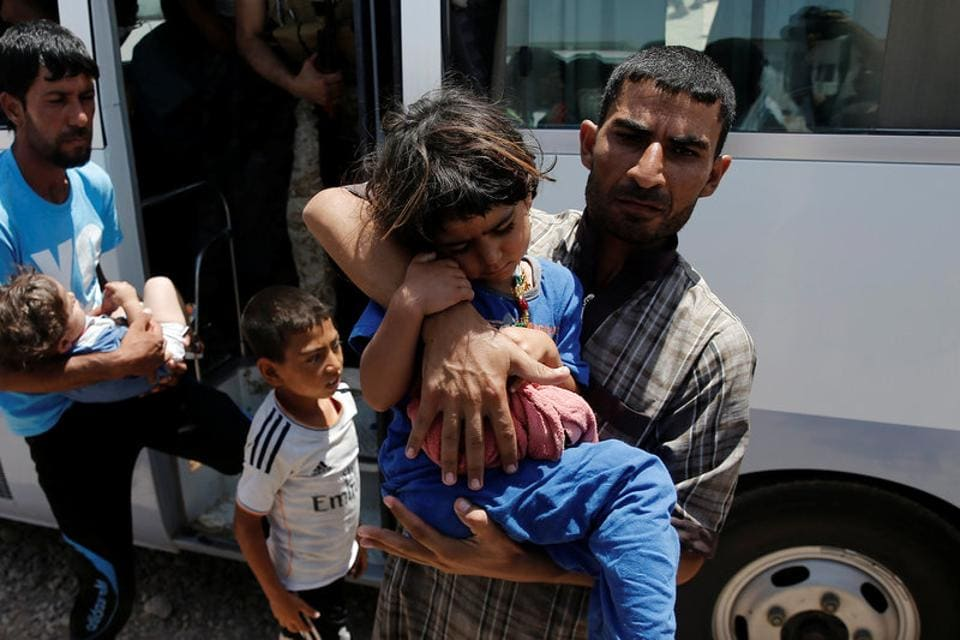 Displaced Iraqi people who fell ill in a mass outbreak of food poisoning, return on a bus after being treated in regional hospitals, at the Hasansham U2 camp in al-Khazer, east of Mosul, Iraq June 13, 2017.