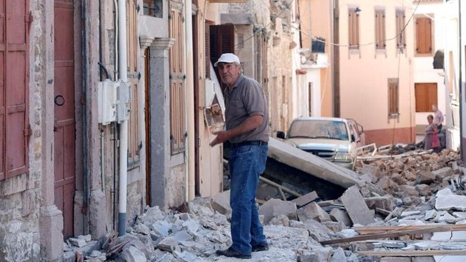 A man stands among damaged buildings at Vrissa , after a strong earthquake shook the eastern Aegean. (Giorgos Moutafis / Reuters )