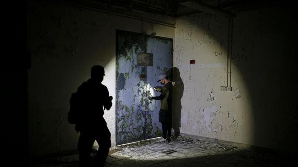 Short videos show the members shining their flashlights on the prison gates of a colonial political prison, a pile of dusty movie reels and posters in an empty movie studio, or the walls of a former World War Two air raid tunnel. (REUTERS)