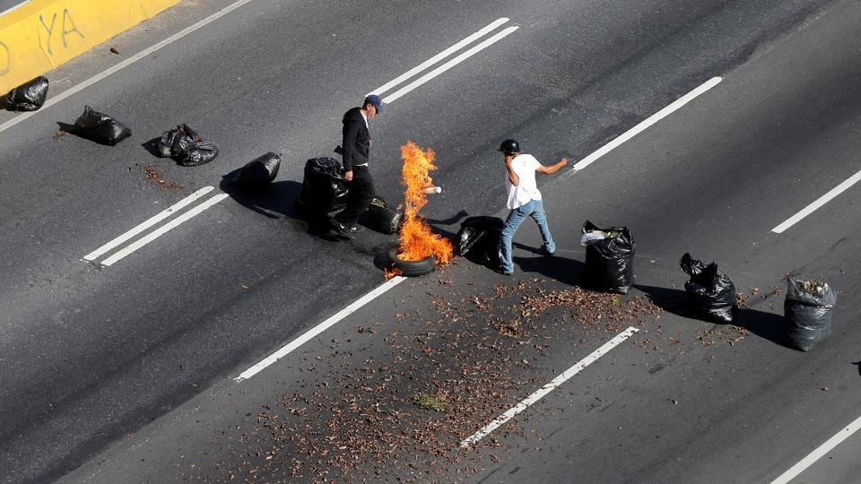 A man sets a tire on fire during protests . (Ivan Alvarado / REUTERS)