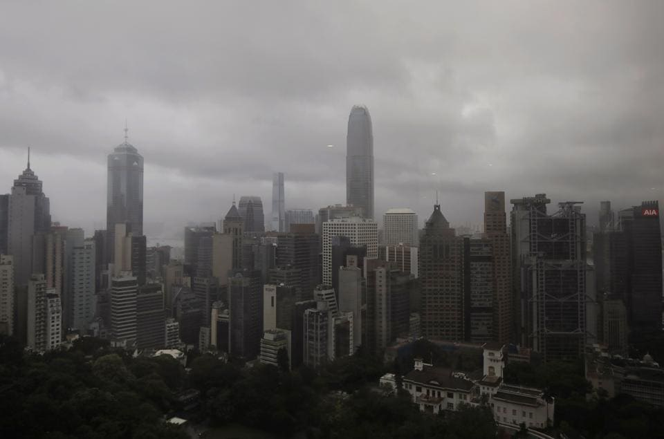 Dark clouds hang low over a business center . Hong Kong lowered the storm signal to No. 3 early on Tuesday and it was expected to remain in force for most of the morning. (Vincent Yu / AP)
