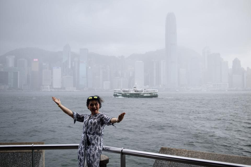A woman poses on a Kowloon promenade in front of the city's skyline. (ANTHONY WALLACE / AFP)