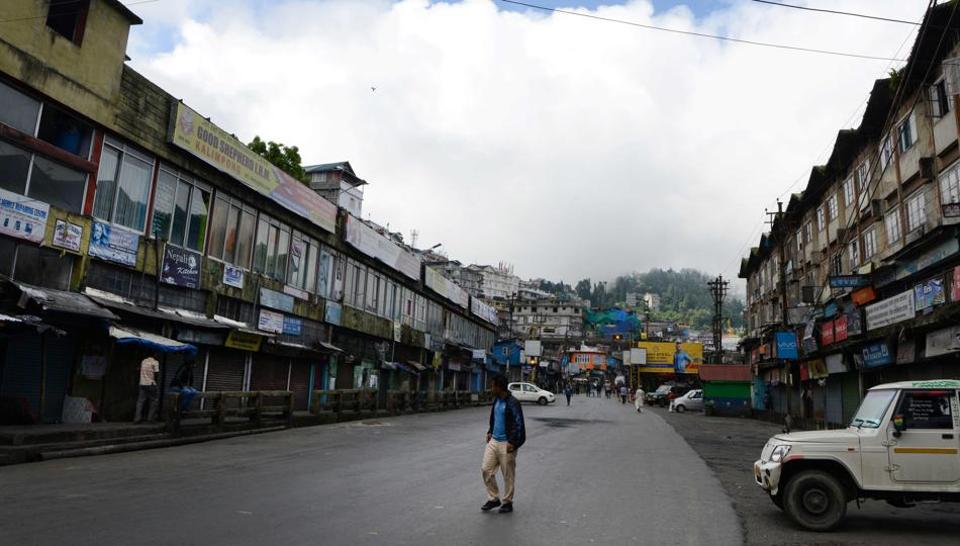 A man walks past shuttered shops during a general strike called by the Gorkha Janmukti Morcha (GJM) in Darjeeling on Tuesday. Thousands of tourists fled the hill station on Monday after local activists demanding the creation of a new state warned that a general strike could degenerate into violence.