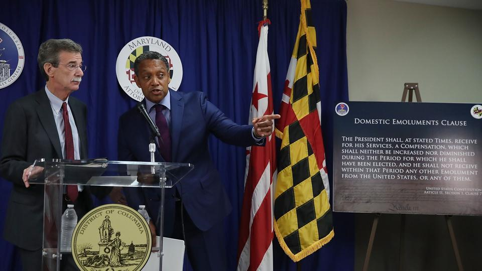 Maryland Attorney General Brian (L) and District of Columbia Attorney General Karl Racine speak to the media about filing a lawsuit against U.S. President Donald Trump, on June 12, 2017 in Washington, DC. The suit alleges that Trump has violated the Constitution by taking payments from foreign governments while being President of the United States.