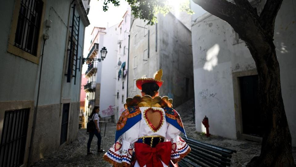 A girl dressed up in traditional costume walks a street of the typical Lisbon neighborhood of Alfama. (PATRICIA DE MELO MOREIRA / AFP)