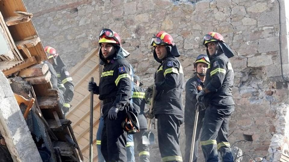 Rescue team members search for victims under a  collapsed building. (Giorgos Moutafis / Reuters )