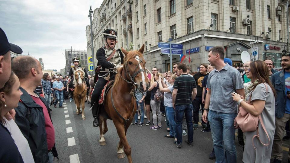 Participants in a history festival taking place on Tverskaya street ride their horses through protesters during an unauthorized opposition rally in central Moscow, Russia. The Russia Day celebrations were crashed by anti-corruption protestors immediately followed by riot police. (Mladen Antonov/AFP)