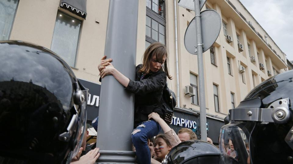 A protestor is pulled down from a lamp post during a demonstration in downtown Moscow, Russia. Russian opposition leader Alexei Navalny aimed to repeat the nationwide protests that rattled the Kremlin three months ago with this nationwide call.  (Alexander Zemlianichenko/AP)