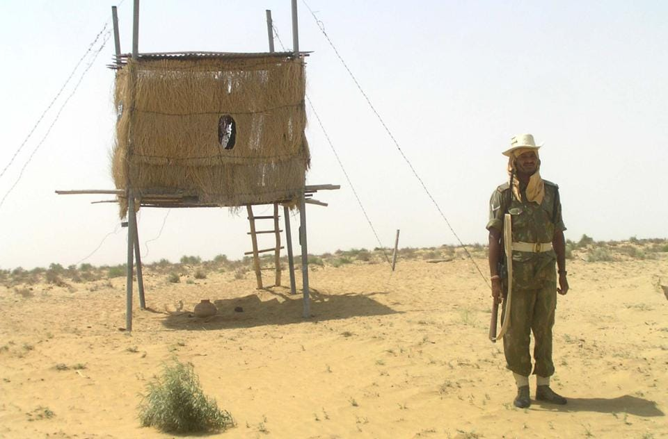 Soldier atop sand dunes at international Border.