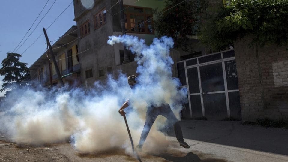 A Kashmiri protester throws a tear gas shell back at police forces during a protest in Srinagar, with parts of the valley remaining under curfew with Kashmiri separatists calling for strikes to protest the killing of a civilian by security forces last week. Police busted a Hizbul Mujahideen module when they arrested two militants in Jammu and Kashmir's Handwara on Monday, 12th June. Two supporters of the militant outfit were also nabbed in Awantipora. (AP)