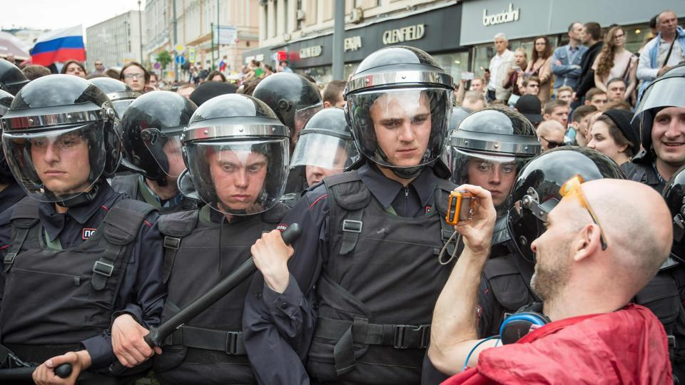 A participant takes a picture of  riot police on Tverskaya street in central Moscow, Russia. Police rounded up demonstrators with slogans of 'Shame!', 'Putin is a thief!' and 'Freedom to Navalny!' ringing in the air. (Mladen Antonov/AFP)