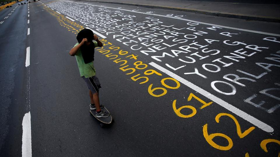 A demonstrator rolls a skateboard next to a list of the victims of the violence during protests against Venezuela's president Nicolas Maduro government in Caracas, Venezuela.  The deadly unrest in Venezuela could lead to 'a blood bath' and spark a major refugee crisis, Peru's President Pedro Pablo Kuczynski warned as violence continued in Venezuela's capital, Caracas. (Ivan Alvarado / REUTERS)