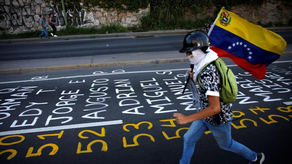 A demonstrator carries a Venezuelan flag as he runs next to a list . Anti-government protesters want new elections and have called for President Nicolas Maduro's resignation.  (Ivan Alvarado / REUTERS)
