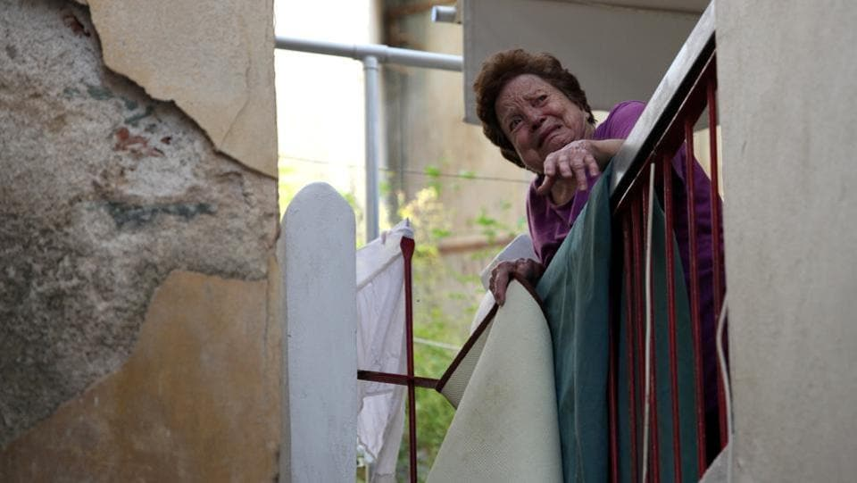 A woman reacts as she stands on her balcony at the village of Plomari. (Elias Marcou / REUTERS)