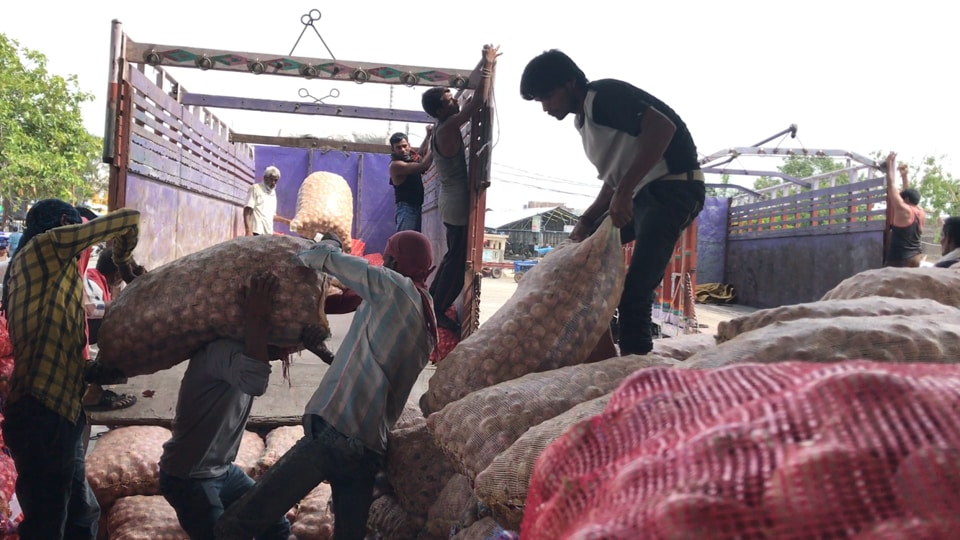 Labourers load sacks of onion on a truck at a government procurement centre in Ujjain.  The Madhya Pradesh government opened the centres in the wake of farmers' stir in Mandsaur.