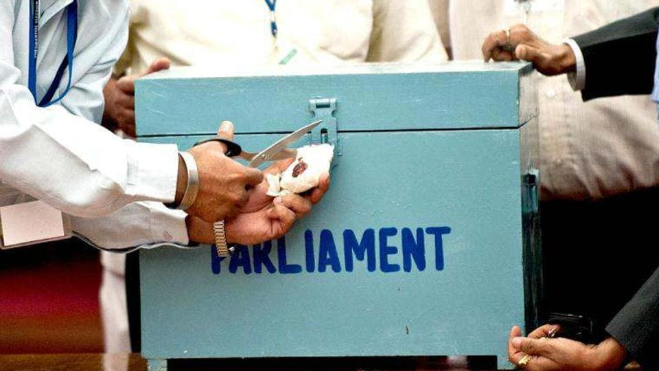 Election observers and officials open the seal of a ballot box as they begin tallying the presidential election results, at the Parliament in New Delhi.