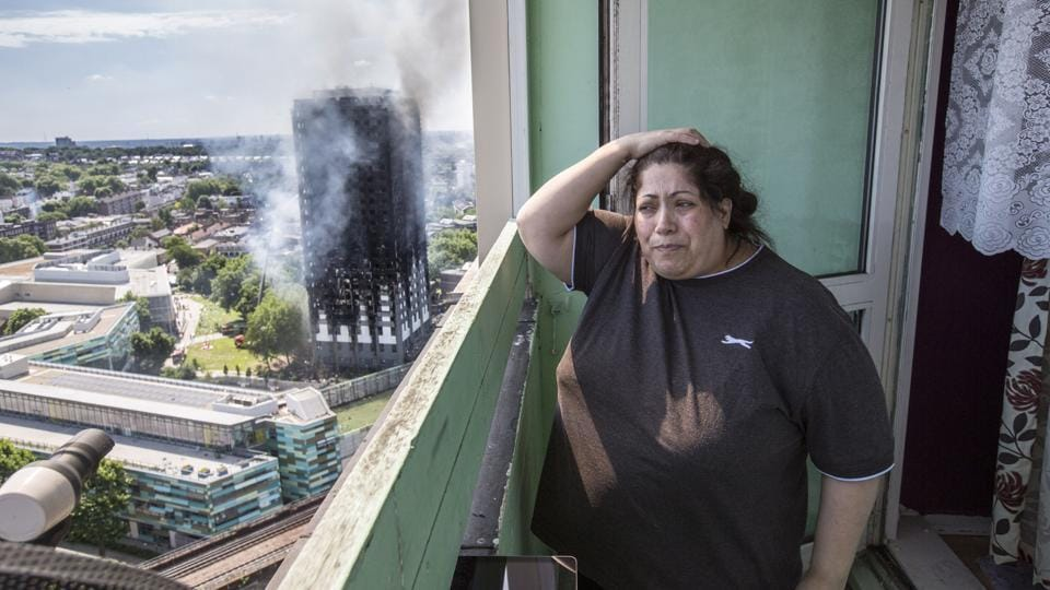 Local resident Georgina stands distraught on her balcony after a fire engulfed the 24-storey Grenfell Tower. (Rick Findler / AP)