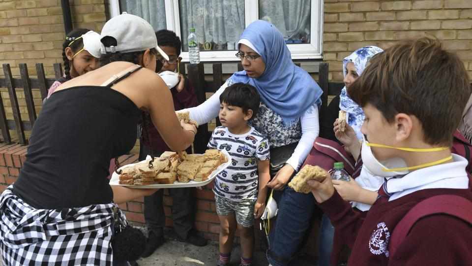 Sandwiches are handed out to local residents close to a fire that has engulfed the 24-storey Grenfell Tower in west London, Wednesday June 14, 2017. Fire swept through a high-rise apartment building in west London early Wednesday, killing an unknown number of people with around 50 people being taken to hospital.