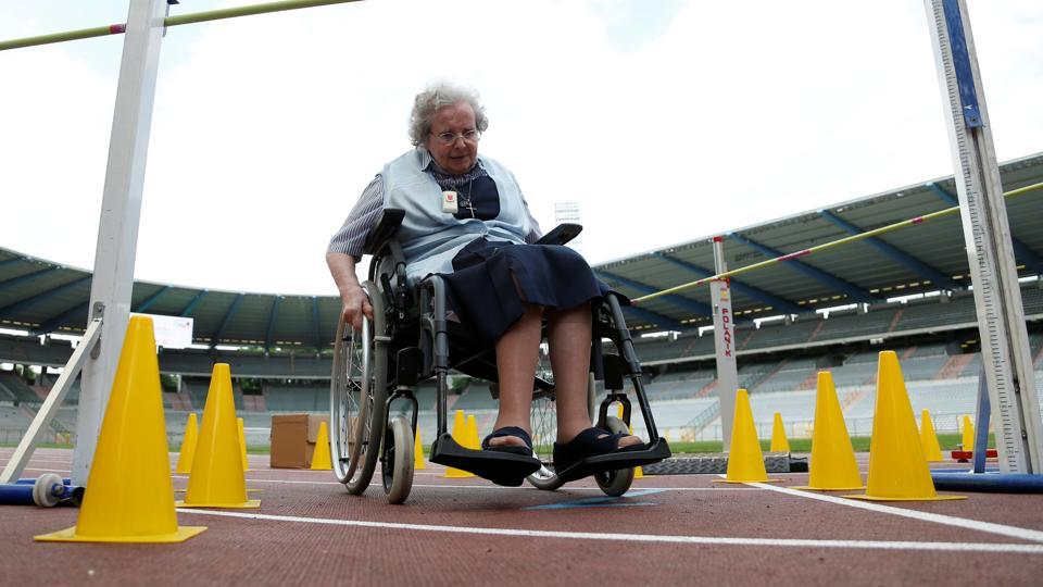 A participant sits in a wheelchair as she takes part in the steeple chase event. (Francois Lenoir / REUTERS)