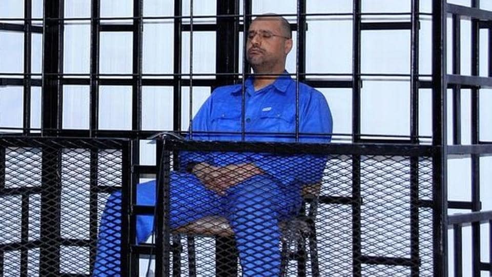 FILE PHOTO: Saif al-Islam Gaddafi, son of late Libyan leader Muammar Gaddafi, attends a hearing behind bars in a courtroom in Zintan May 25, 2014. REUTERS/Stringer/File Photo