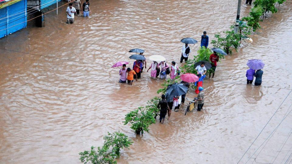 People make their way through a flooded street after heavy rainfall . (PTI)
