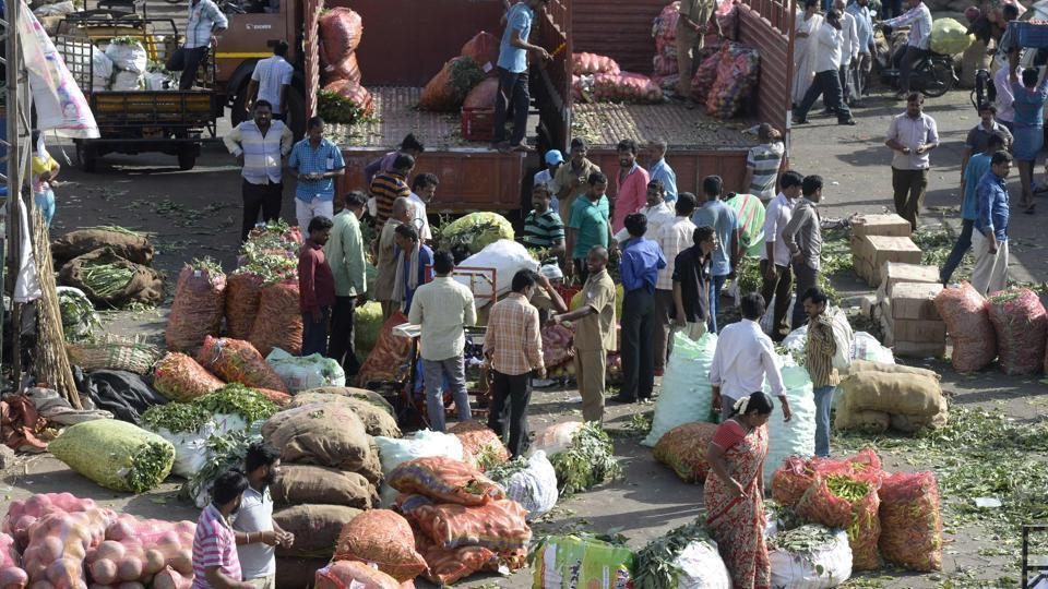 Traders and vendors negotiate prices of vegetables at a wholesale vegetable market in Hyderabad.