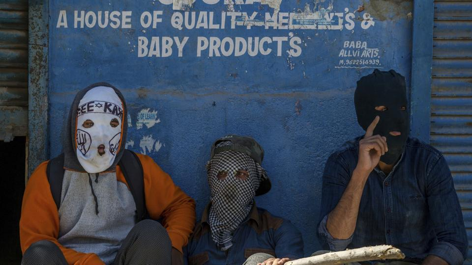 Masked Kashmiri protesters take a break from throwing stones at Indian police men during a protest in Srinagar, Indian controlled Kashmir, Friday, June 9, 2017.