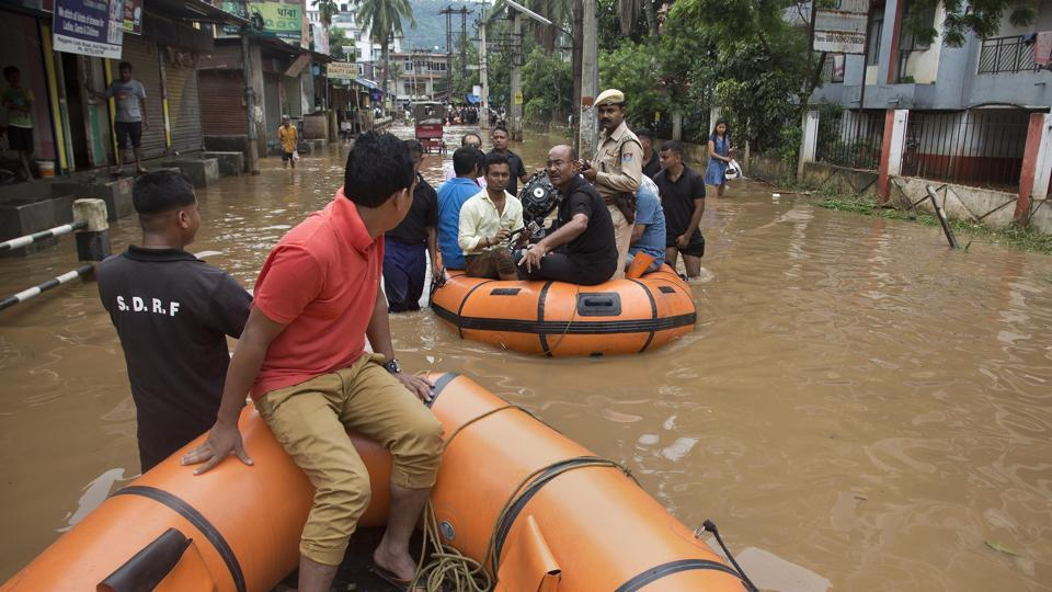State Disaster Response Force personnel arrive on rafts to rescue flood affected people through a road waterlogged in Tuesday's monsoon rain in Guwahati, Assam, India, June 14, 2017.