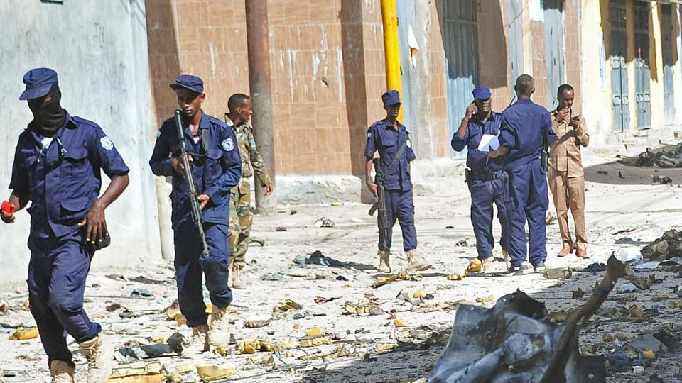 Somali security forces and civilians gather at the scene of a car bomb attack in Mogadishu on May, 15, 2017.