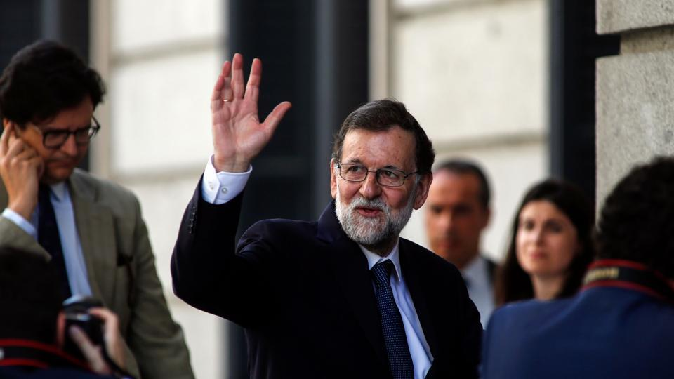 Spanish Prime Minister Mariano Rajoy waves as he arrives at the Congress of Deputies (Las Cortes) in Madrid on June 14, 2017 before a vote of no confidence tabled by the far-left Podemos to denounce a series of corruption scandals that have hit the Prime Minister's conservative party.