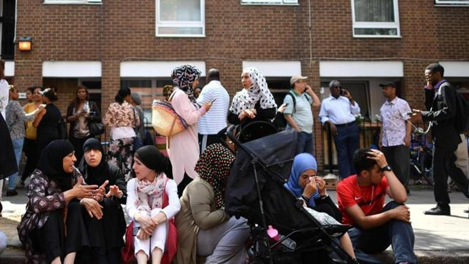People affected by the fire that ripped through Grenfell Tower, a residential block sit on the pavement outside a temporary aid centre in west London on June 14, 2017. At least six people were killed Wednesday when a massive fire tore through a London apartment block overnight, with survivors voicing anger over longstanding safety fears at the 24-storey Grenfell Tower.