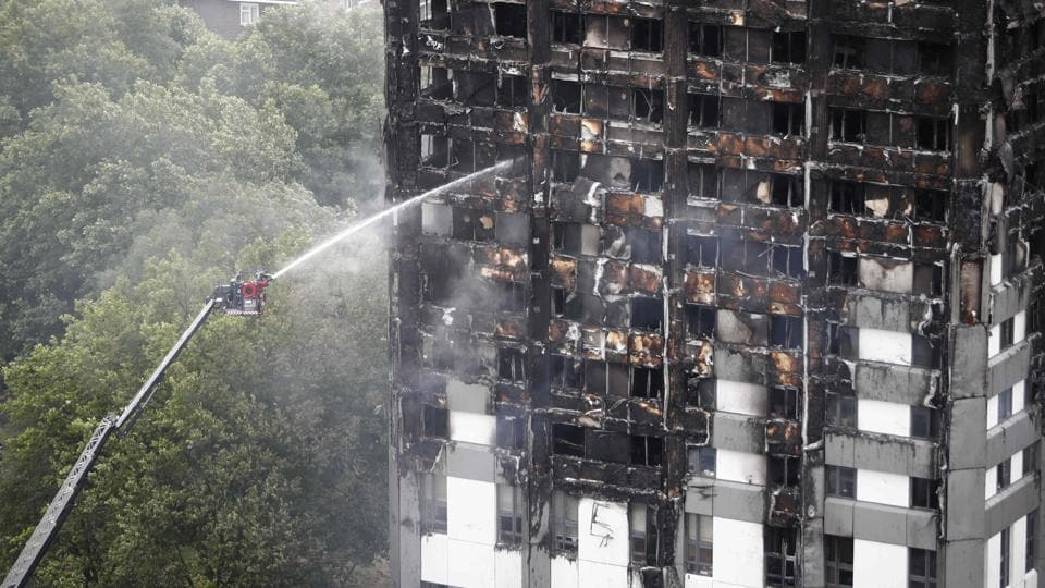 An automated hose sprays water onto Grenfell Tower, a residential tower block in west London that was caught in a huge blaze on June 14, 2017.