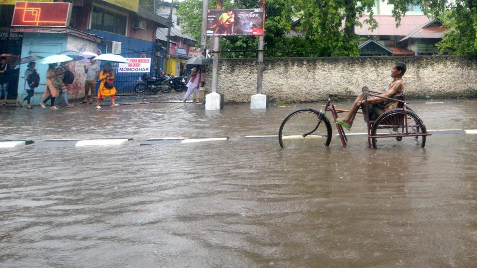 A disabled person wading through a flooded street after heavy rainfall in Guwahati, Assam on Tuesday. (PTI)