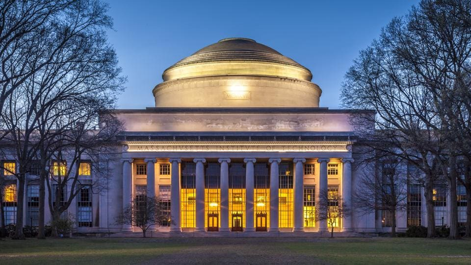The main building of the Massachusetts Institute of Technology in Cambridge, MA, USA showcasing its neoclassic architecture at sunset.