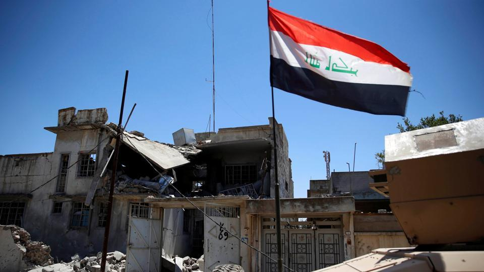 An Iraqi flag attached to an Iraqi military armoured fighting vehicle (AFV) flutters past a destroyed house during clashes in the Shifa neighbourhood in western Mosul, Iraq June 15, 2017.
